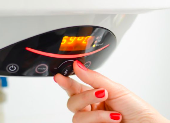 close up of heating controls with woman's hand adjusting a dial